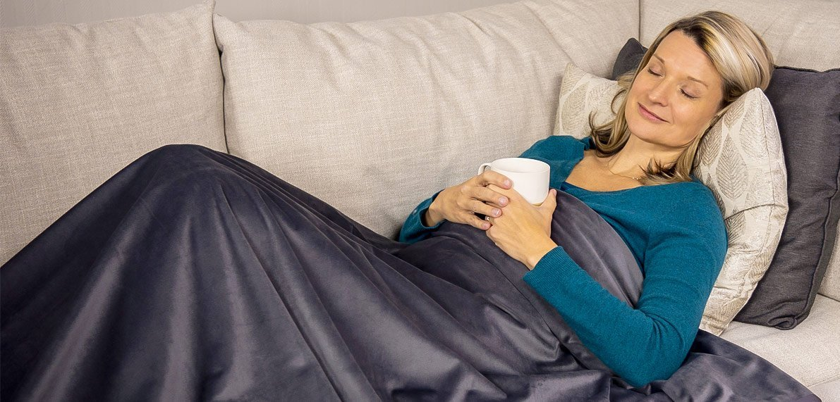 Woman in couch under Remzy blanket
